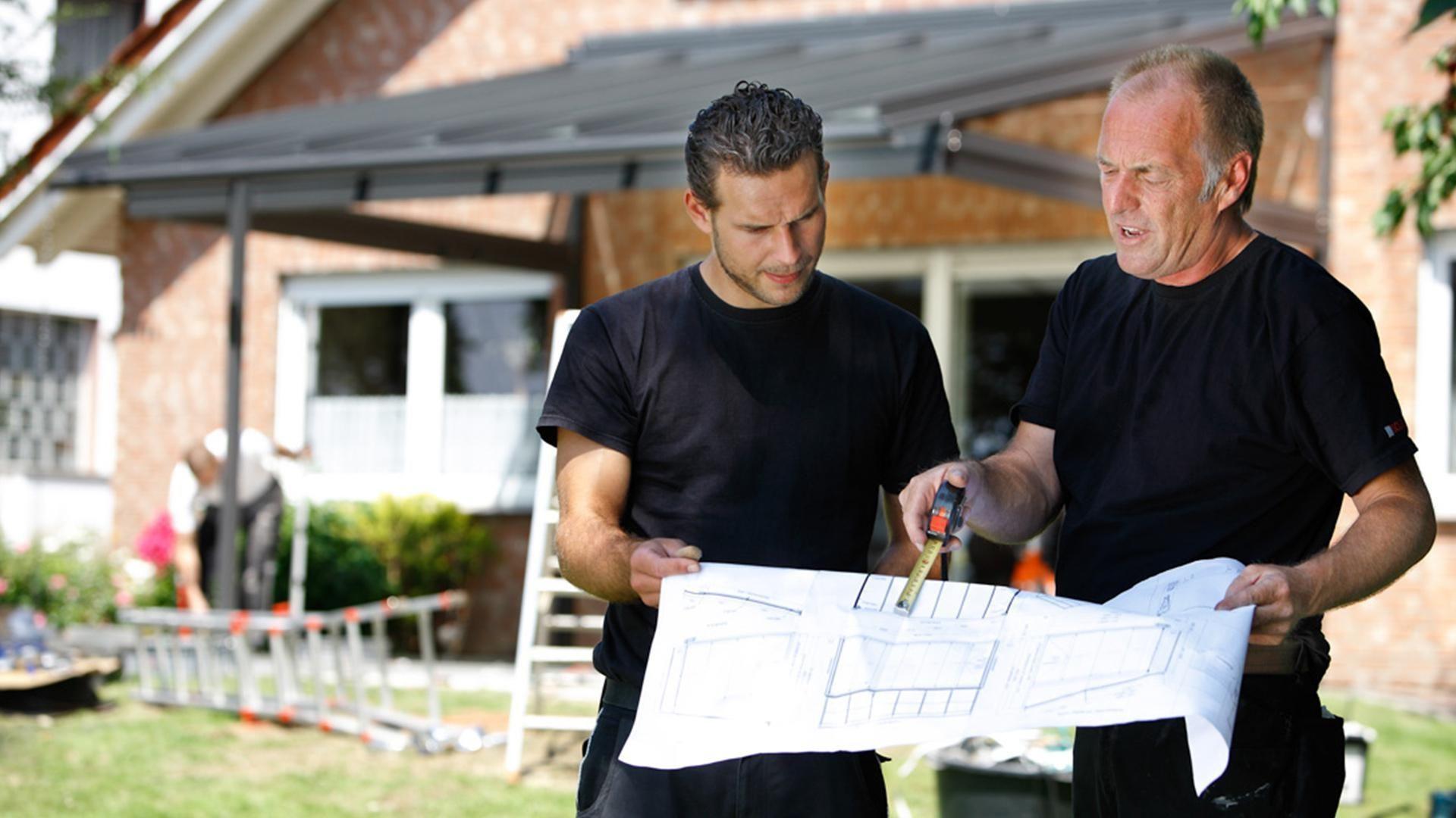 Zwei Männer stehen mit Bauplan vor einen Haus mit Wintergarten