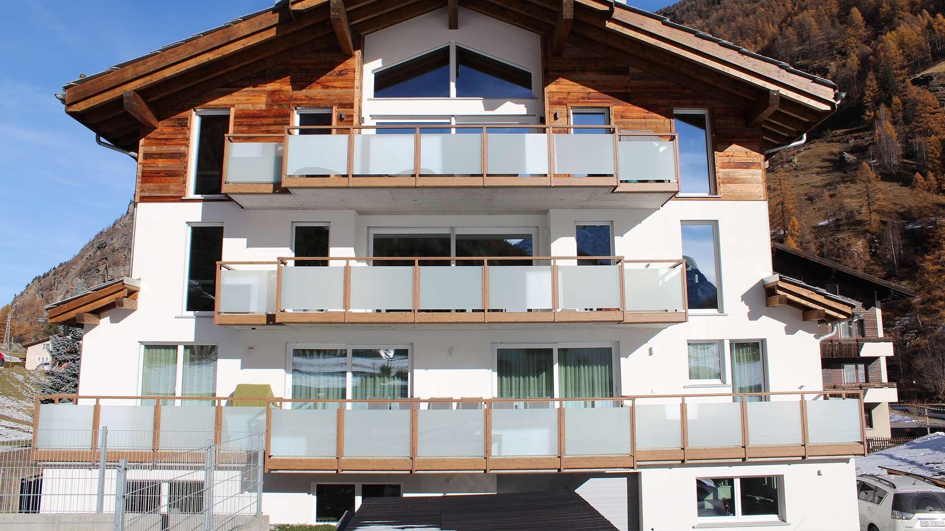 mehrere Balkone mit Alu-Geländer und Glas an einem Haus