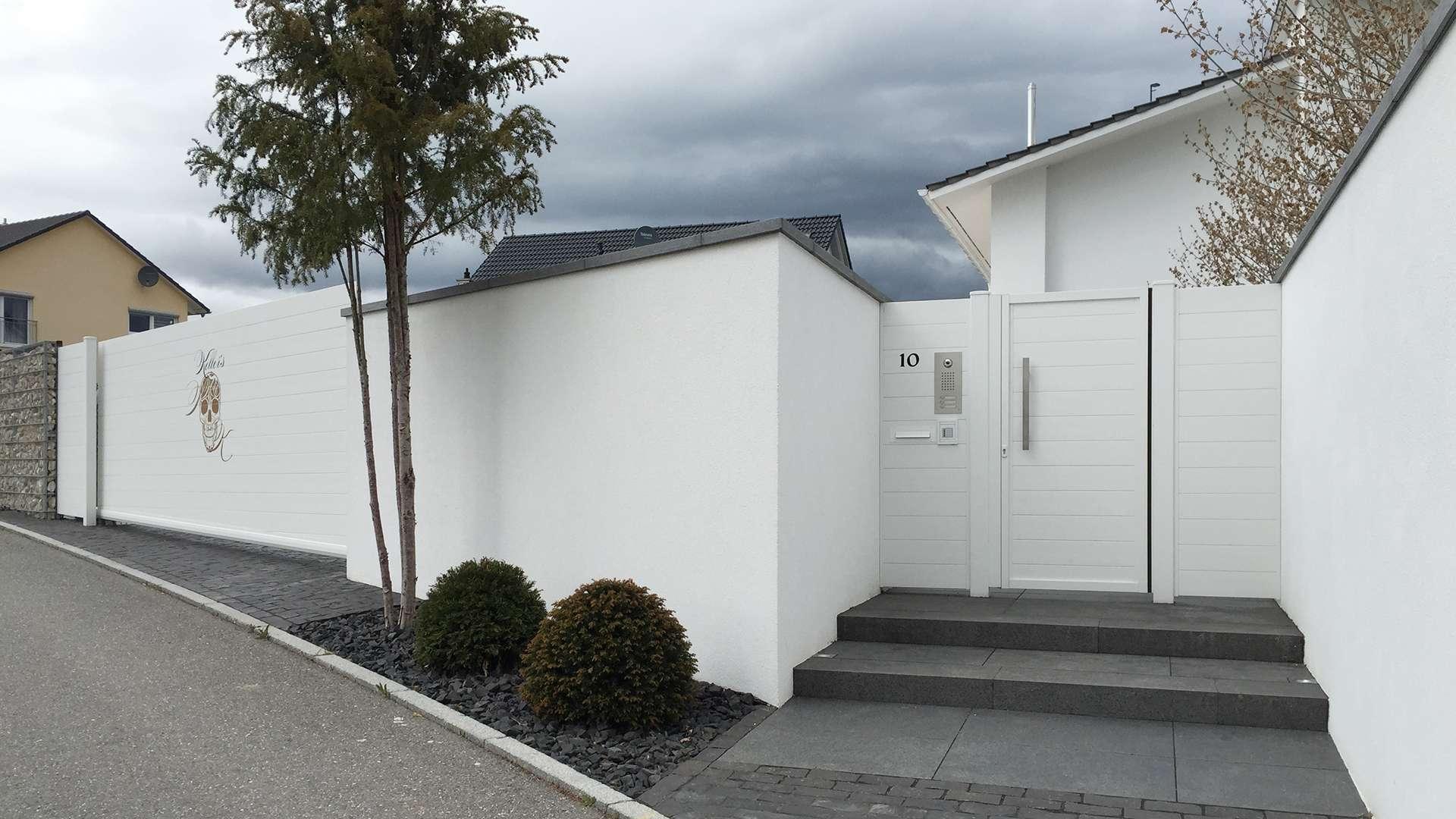 weißes Alu-Tor vor einem Haus