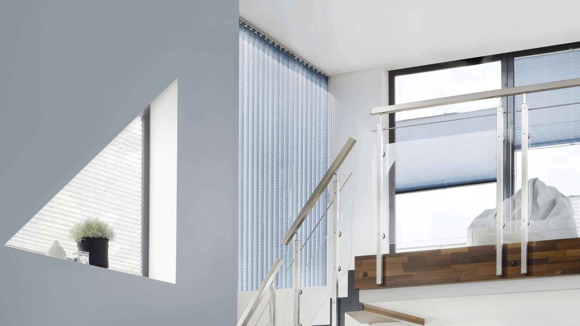 Treppenhaus mit Fenstern unterschiedlichster Form und Plissees davor