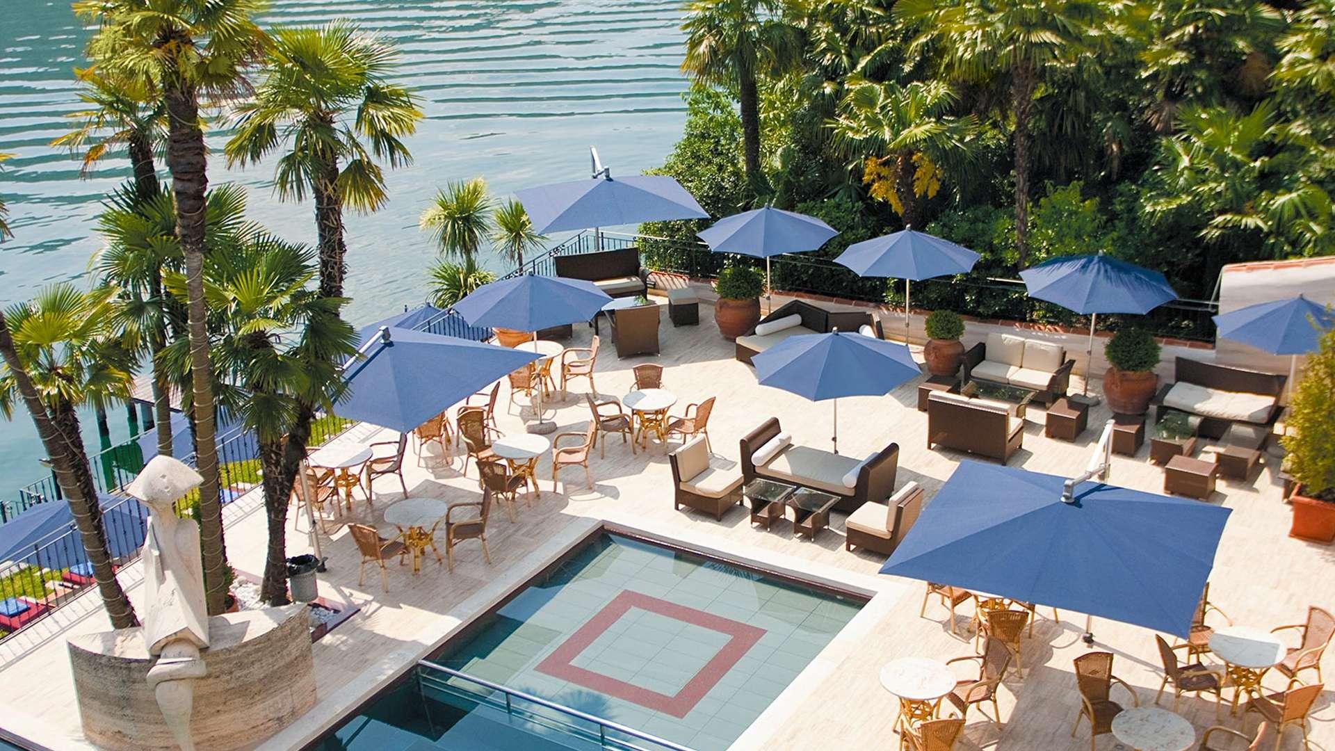 viele blaue Sombrano Sonnenschirme in eckiger und runder Ausführung um einen Hotelpool am Meer