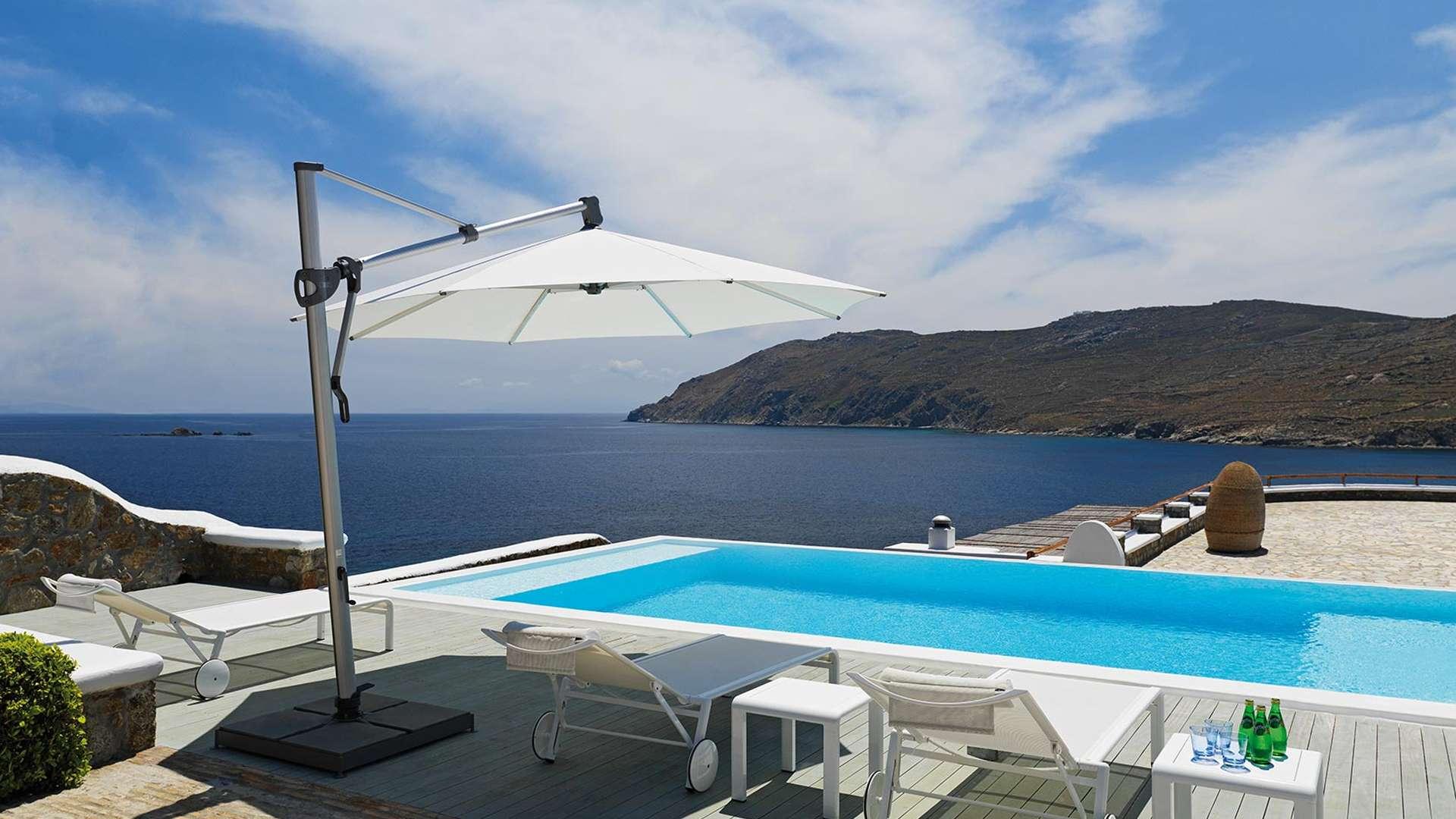 weißer Sombrano Sonnenschirm neben einem Pool am Meer