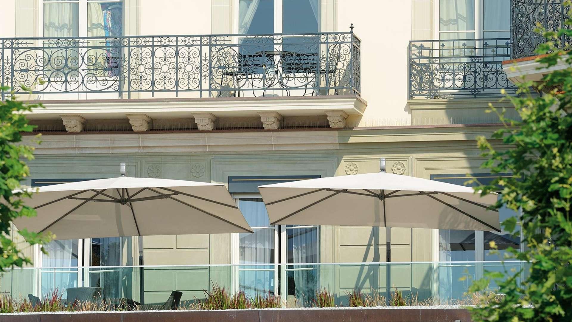 zwei weiße Sombrano Sonnenschirme auf der Terrasse eines Hotels