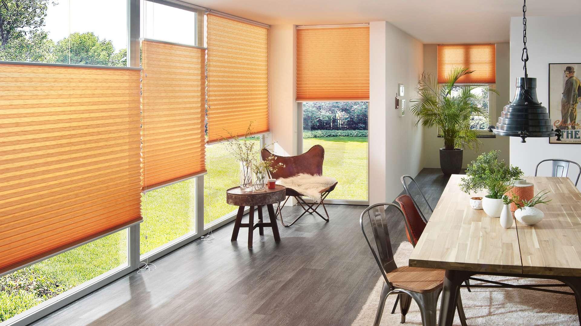 orange Plissees vor den Fenstern eines Esszimmers