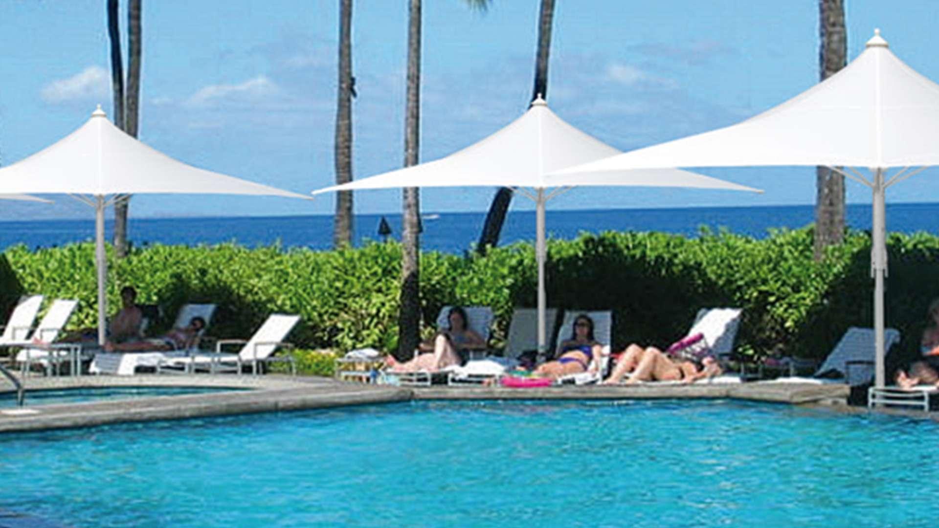 drei Jumbrella Wave Sonnenschirme neben einem Pool