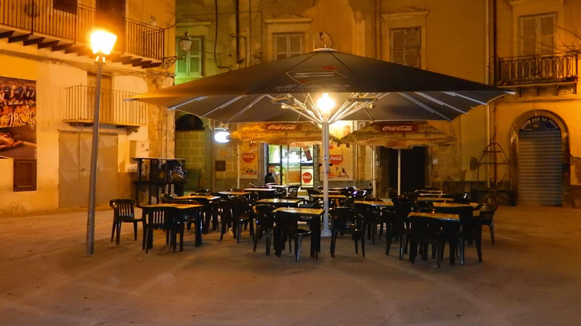 Jumbrella XL Sonnenschirm über mehreren Tisch in der Fußgängerzone bei Nacht