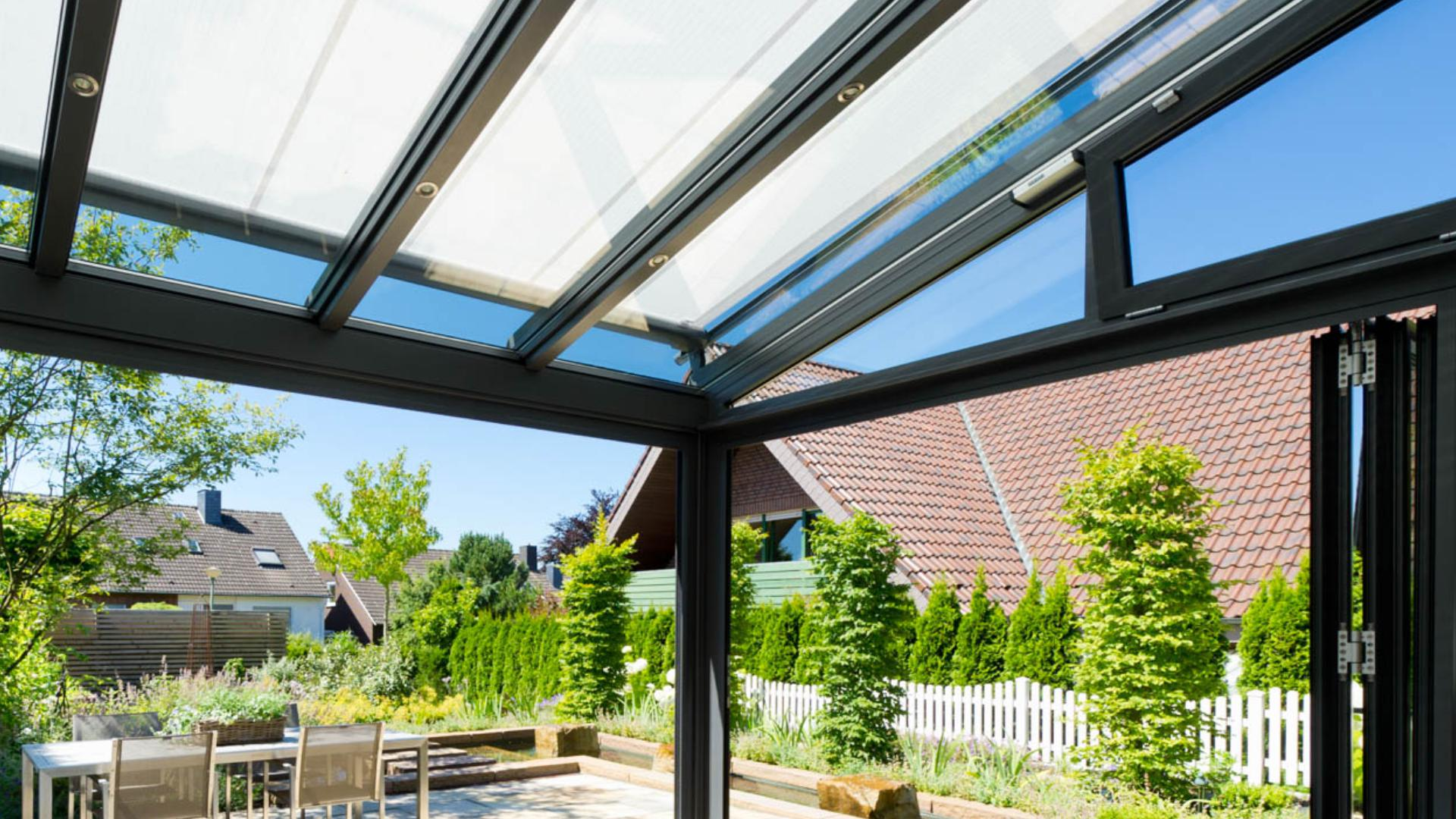 Terrassendach mit Sonnenschutzmarkise mit Blick in einen Vorstadtgarten mit Gartenmöbeln
