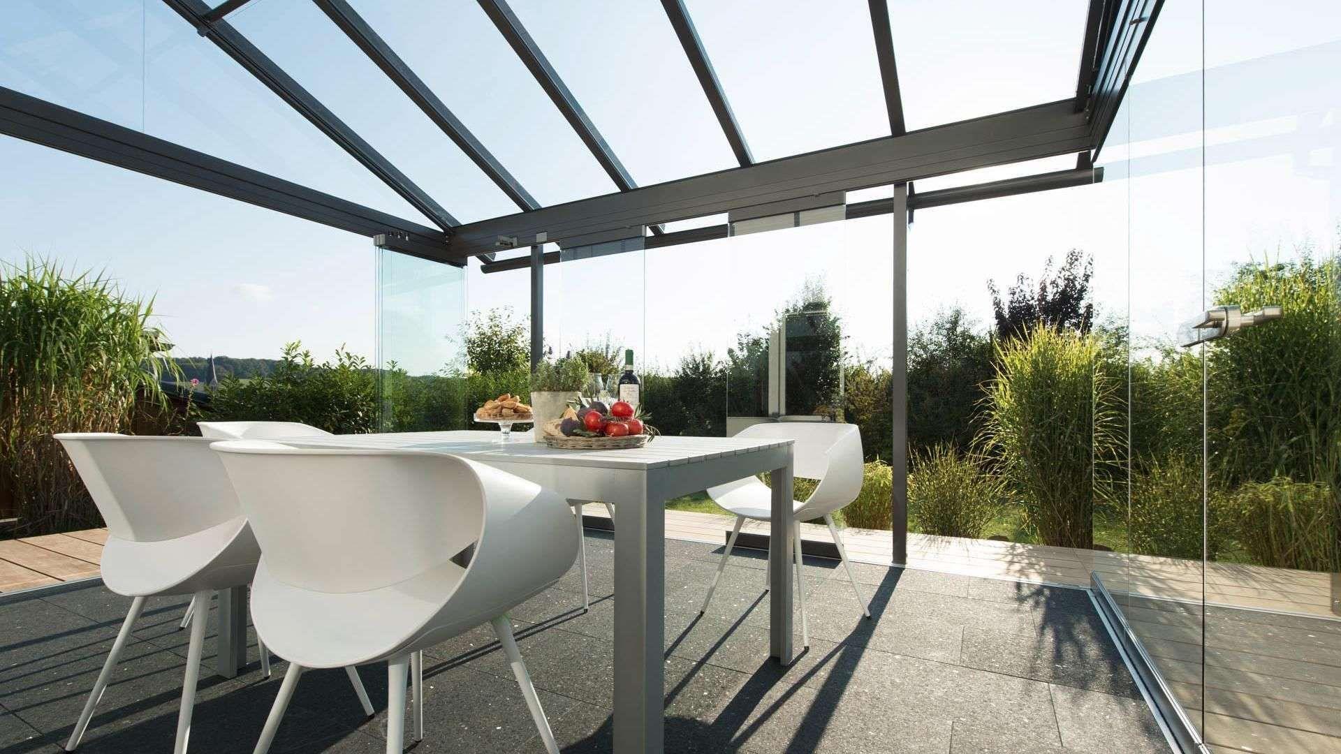 Innenansicht eines Solarlux Glashauses mit geöffneten Glas-Elementen und modernen Sitzmöbeln im Inneren