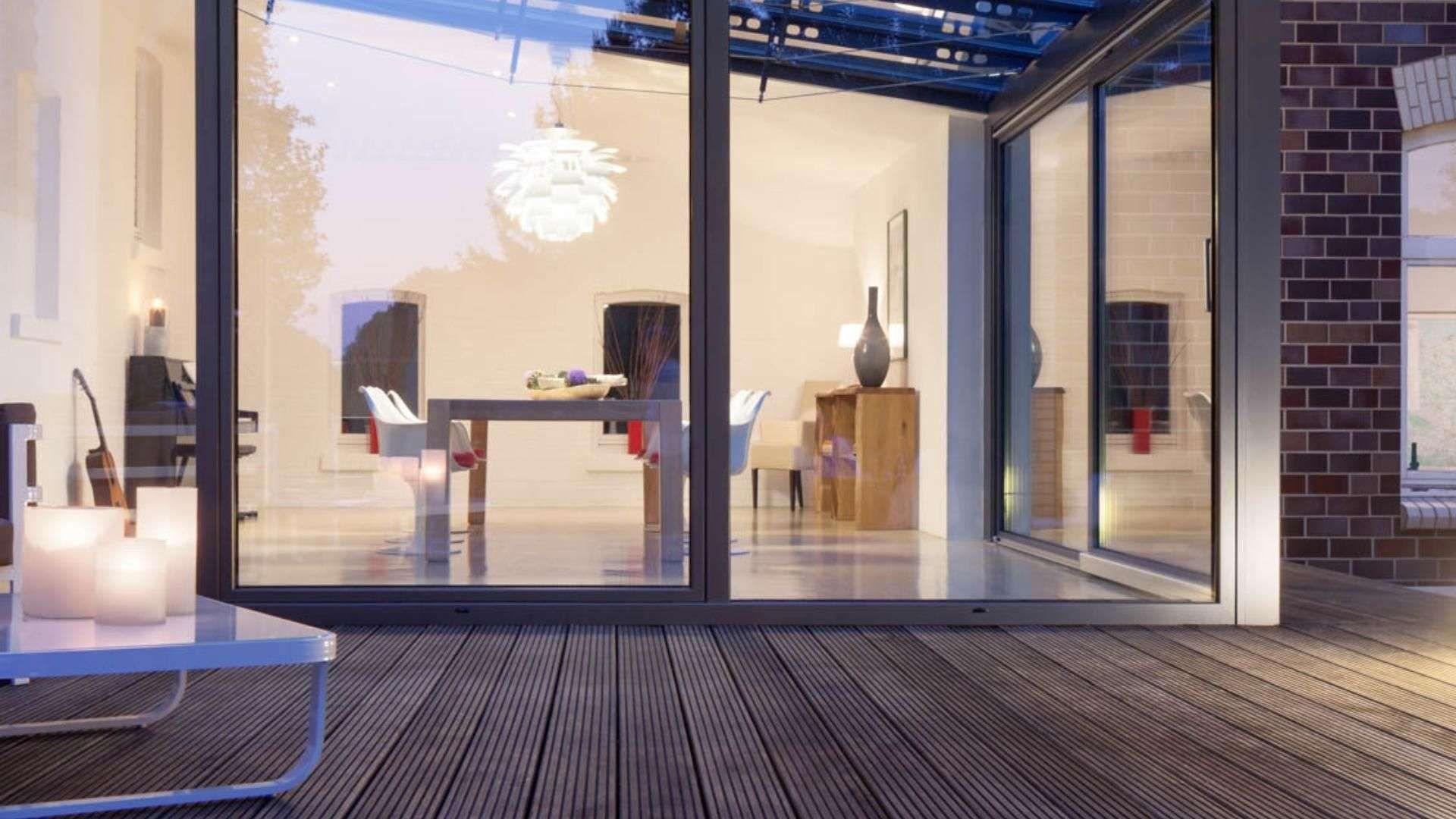 Terrasse mit einem Solarlux SDL Akzent Vision Wintergarten mit Licht und Sitzmöbeln im Inneren