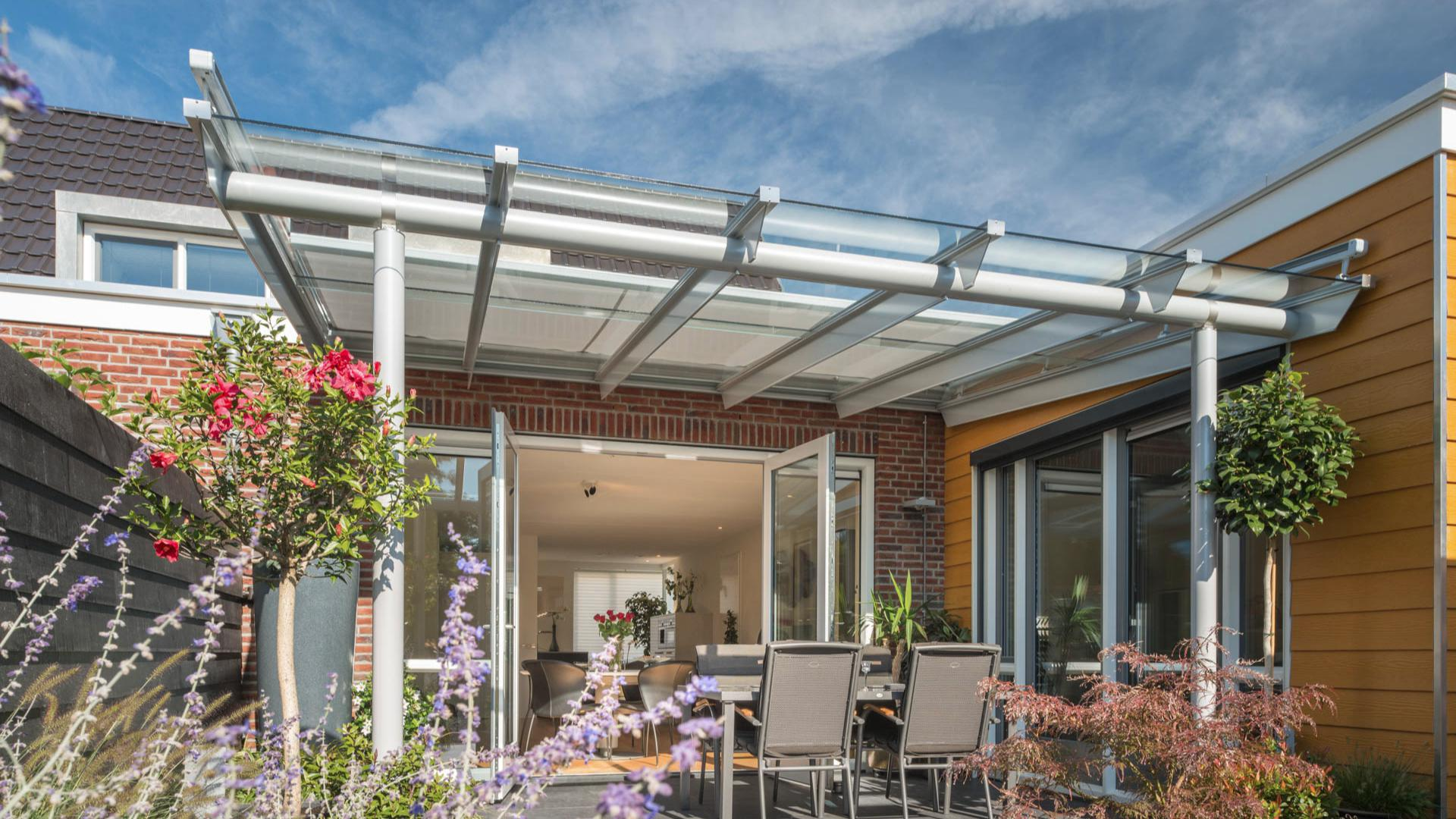 weißes Solarlux Terrassendach in einem Reihenhaus mit Blumen und Gartentisch
