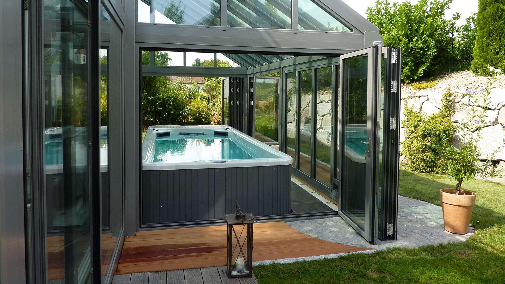 Wintergarten mit geöffneter Glas-Front mit Blick auf einen Indoor-Pool