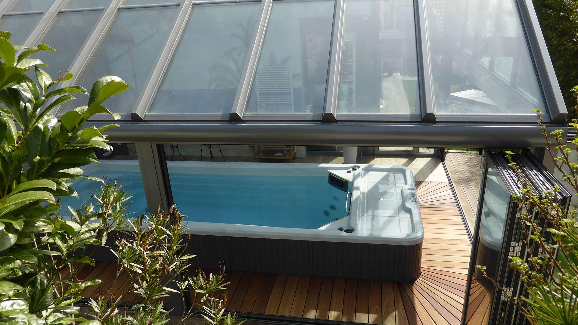 Blick auf einen Wintergarten von oben. Im Inneren steht ein Pool.