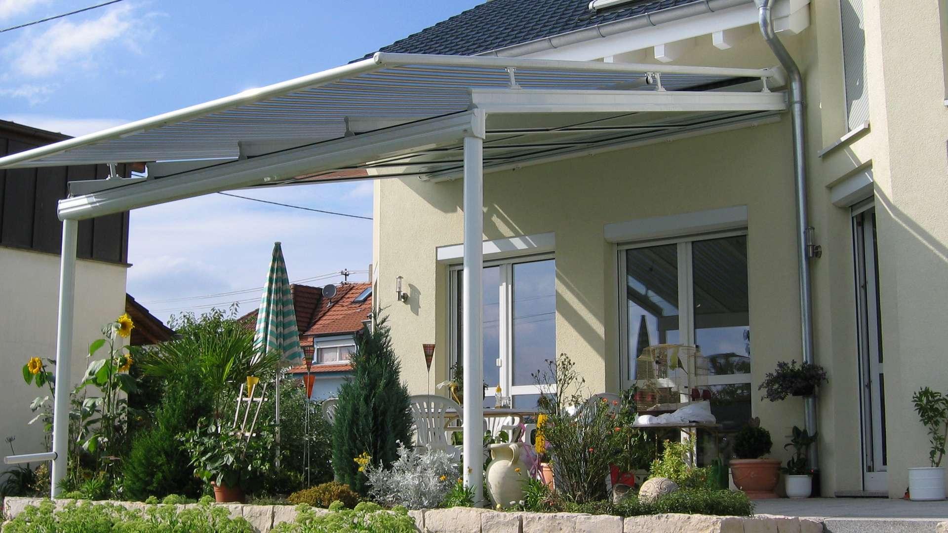 weißes Terrassendach mit Markise an hellgelben Wohnhaus mit bepflanzter Terrasse.
