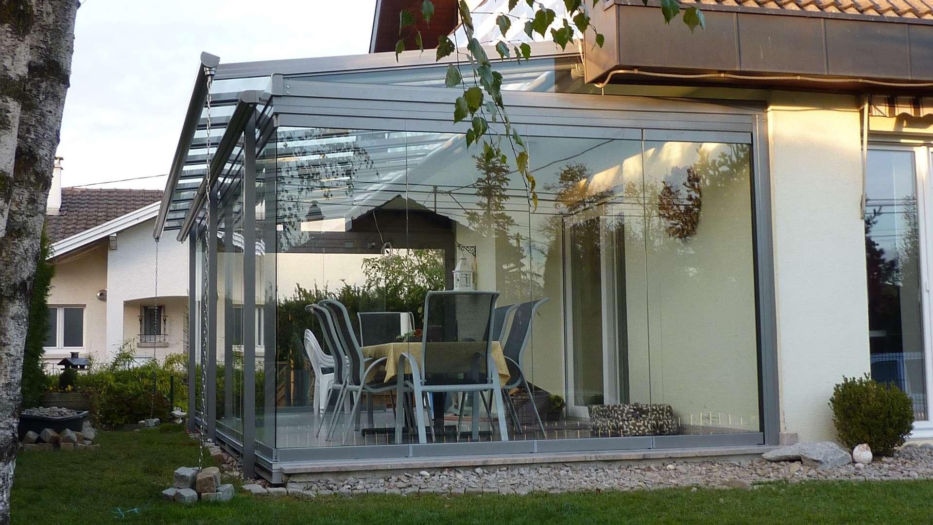Wohnhaus mit Wintergarten mit cero Verglasung. Im Wintergarten steht ein Esstisch.