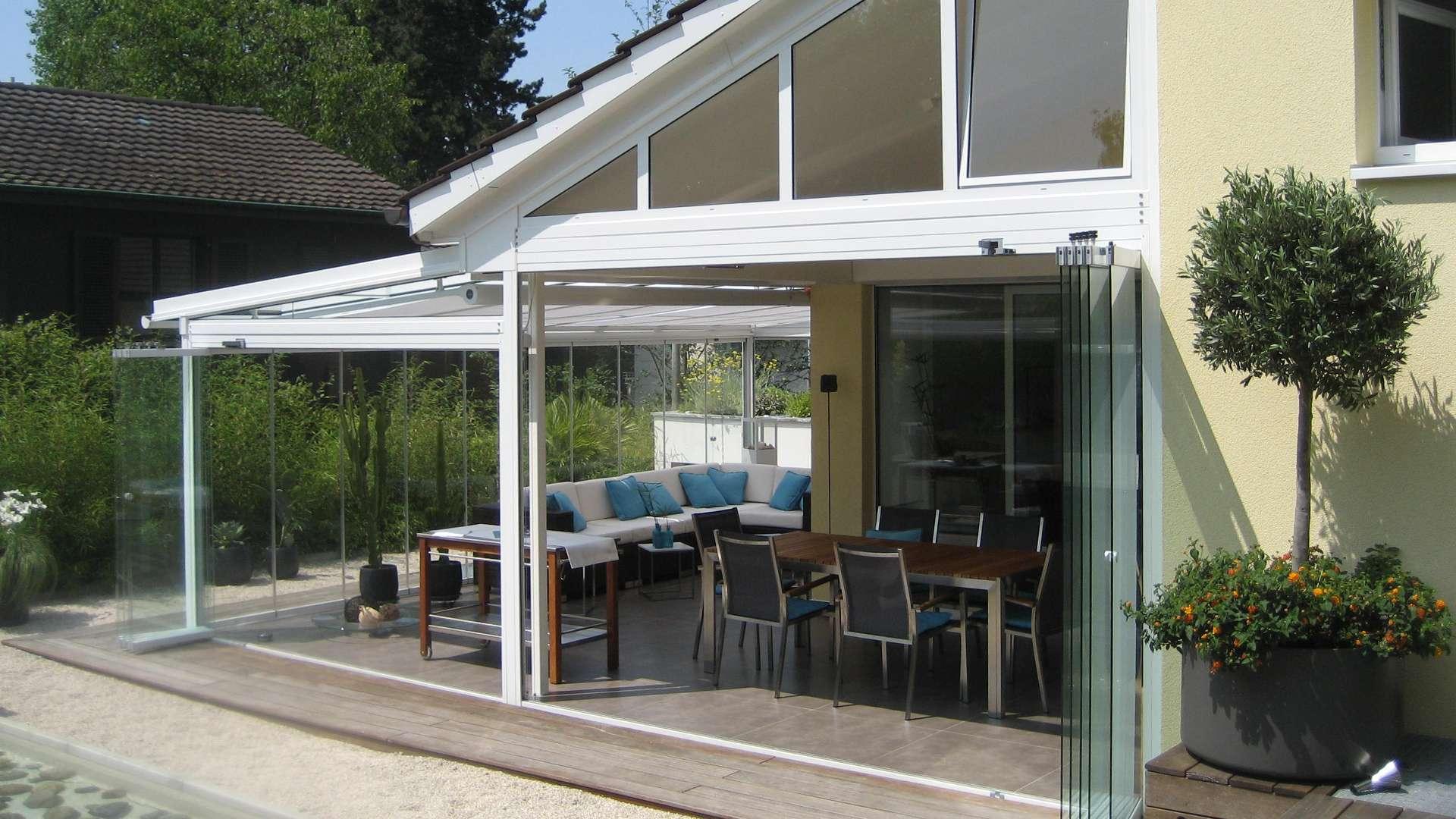 großer weißer Wintergarten an einen Haus mit geöffnter Glasfront