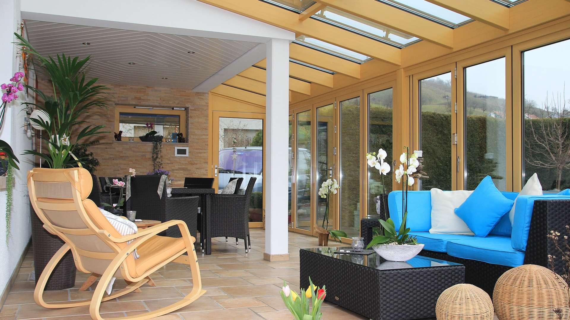 Blick in einen Wintergarten aus Holz mit Sofa und Esstisch im inneren