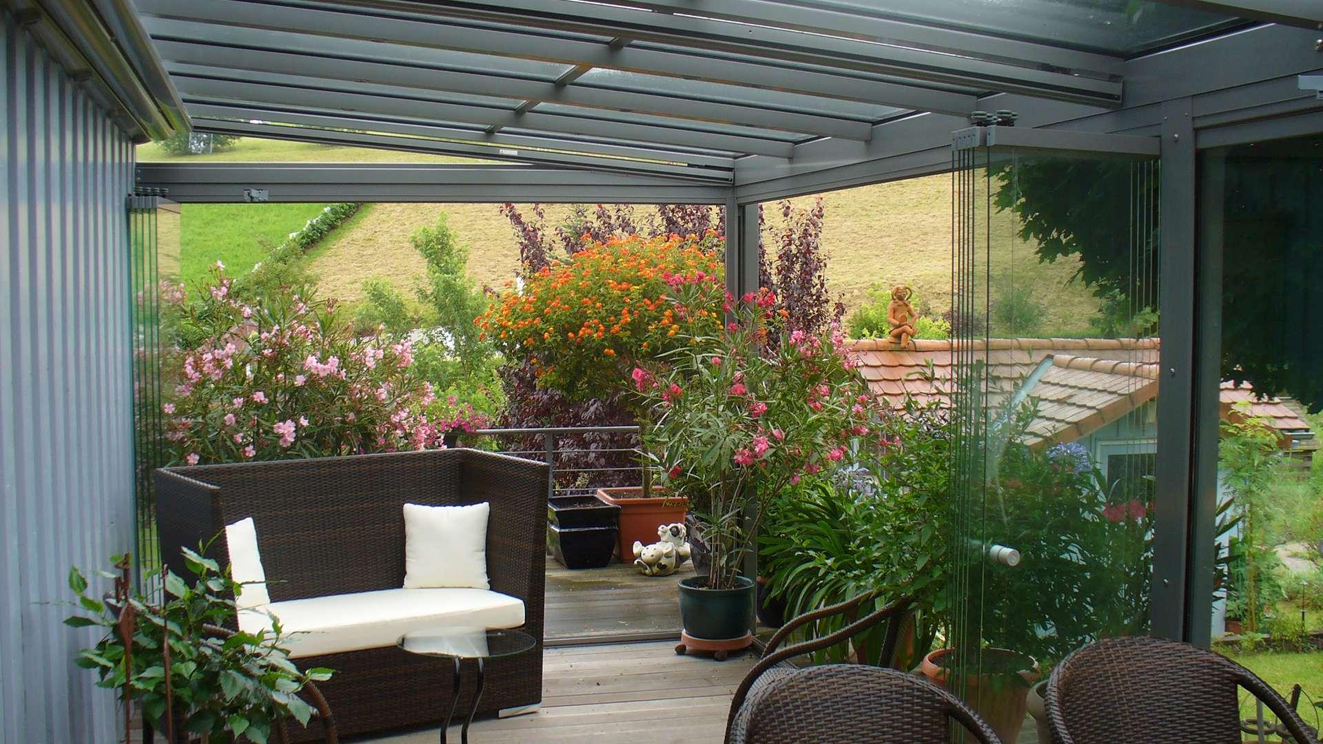 Blick in eine grauen Wintergarten mit Sofa und vielen Pflanzen