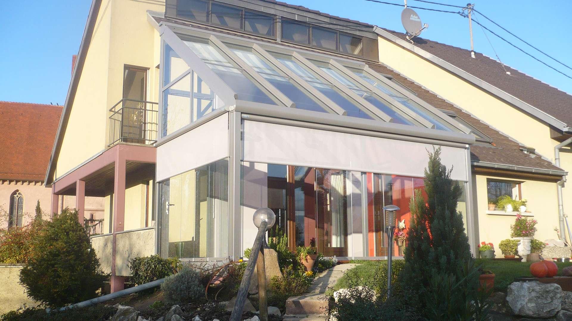 hellgrauer Wintergarten mit Pultdach an einem hellgelben Wohnhaus