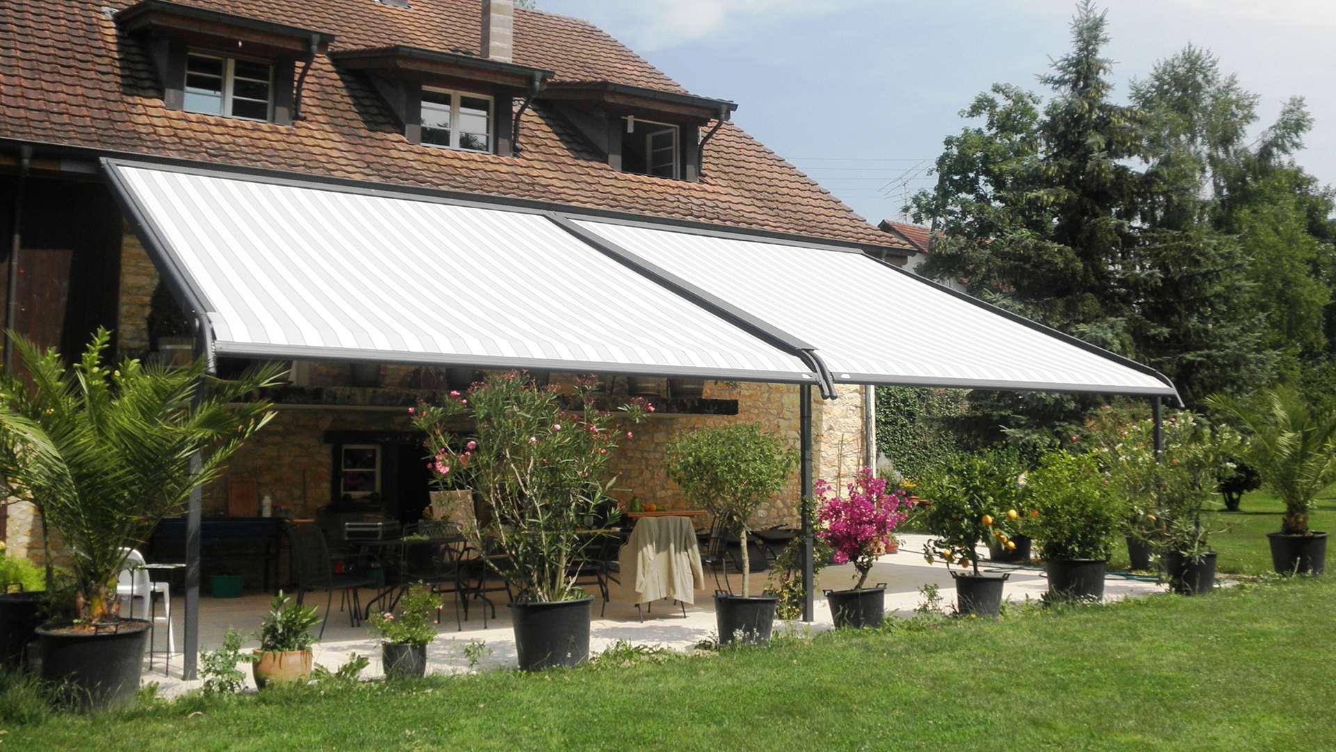 Wohnhaus mit zwei gestreiften Markisen über der Terrase
