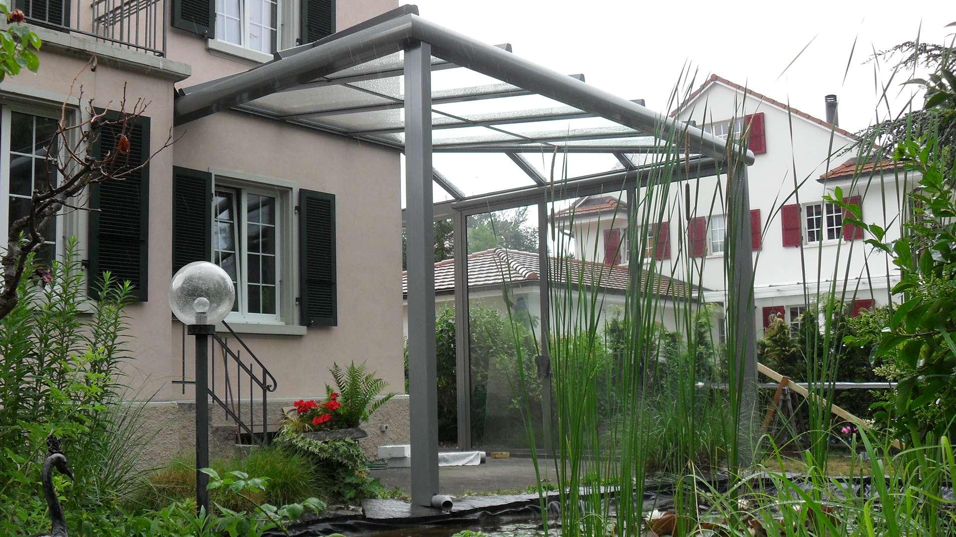 Terrassendach an einen Wohnhaus mit vielen Pflanzen im Garten
