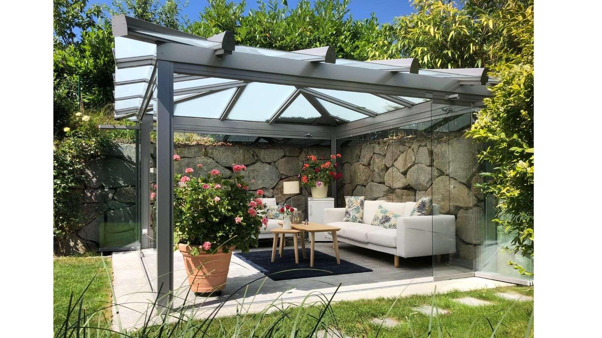 freistehendes Glashaus mit Sofa neben einer Steinmauer