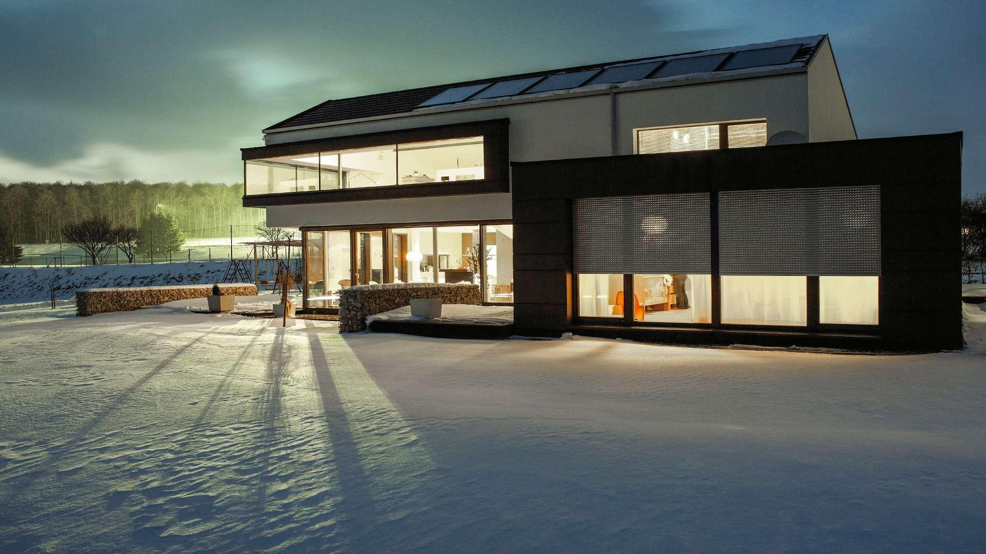 modernes Wohnhaus im Schnee mit Rollläden vor den Fenstern