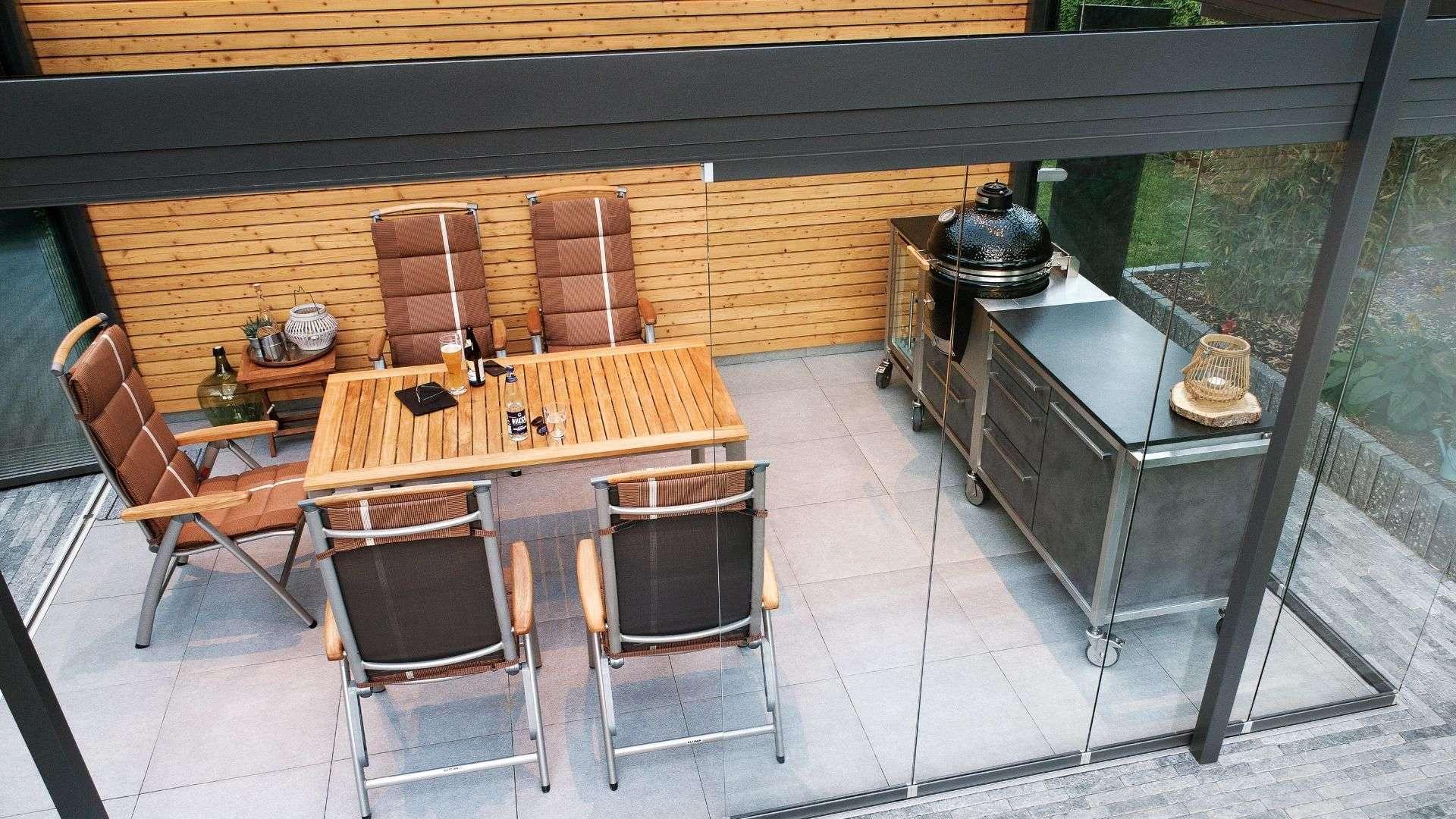 Burnout Outdoorküche mit Esstisch in einem Glashaus