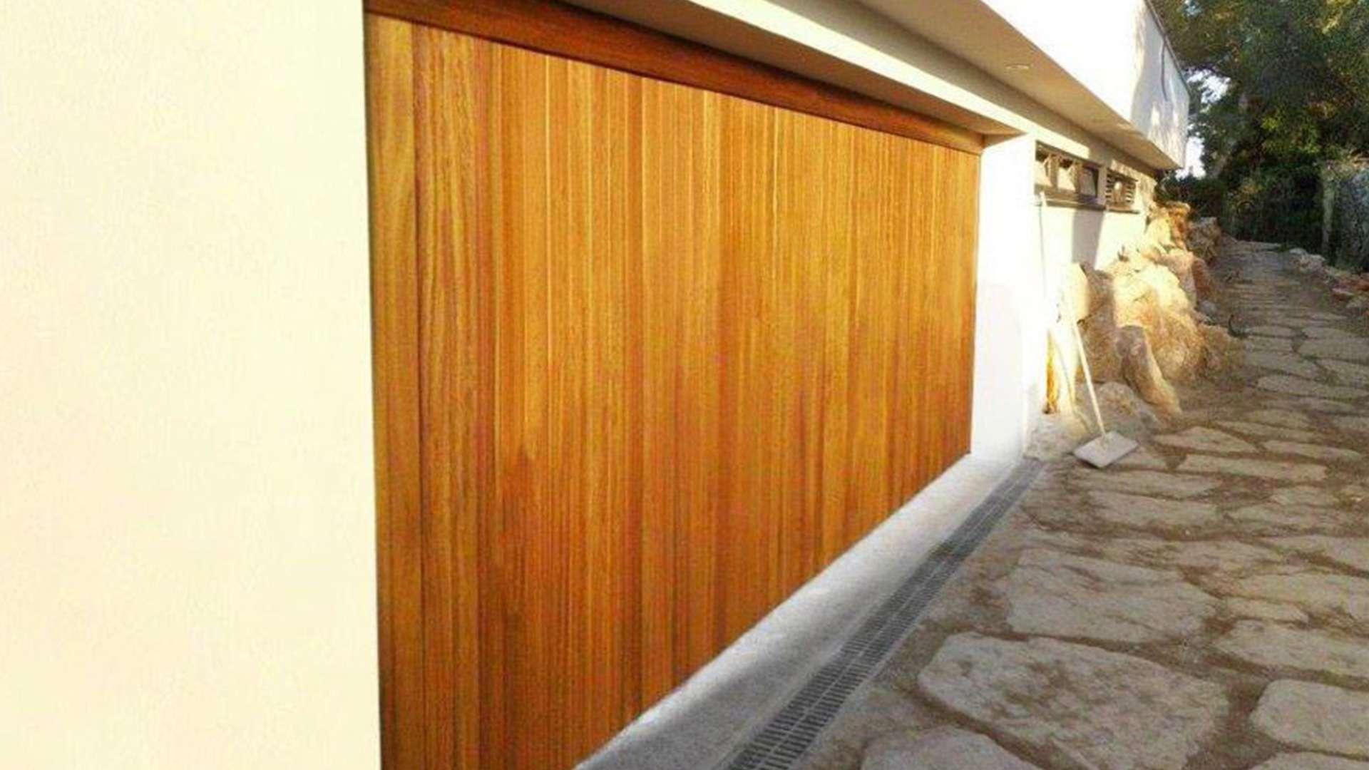 Garagentor aus Holz in heller Fassade