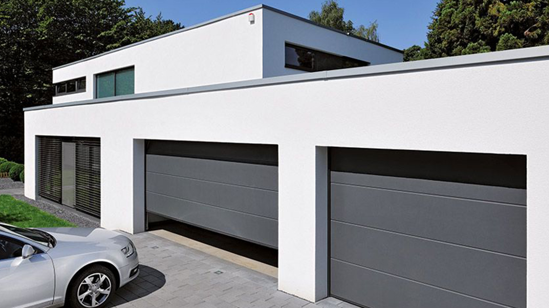 Flachdach-Haus mit zwei Garagentor, von denen eins gerade geöffnet wird