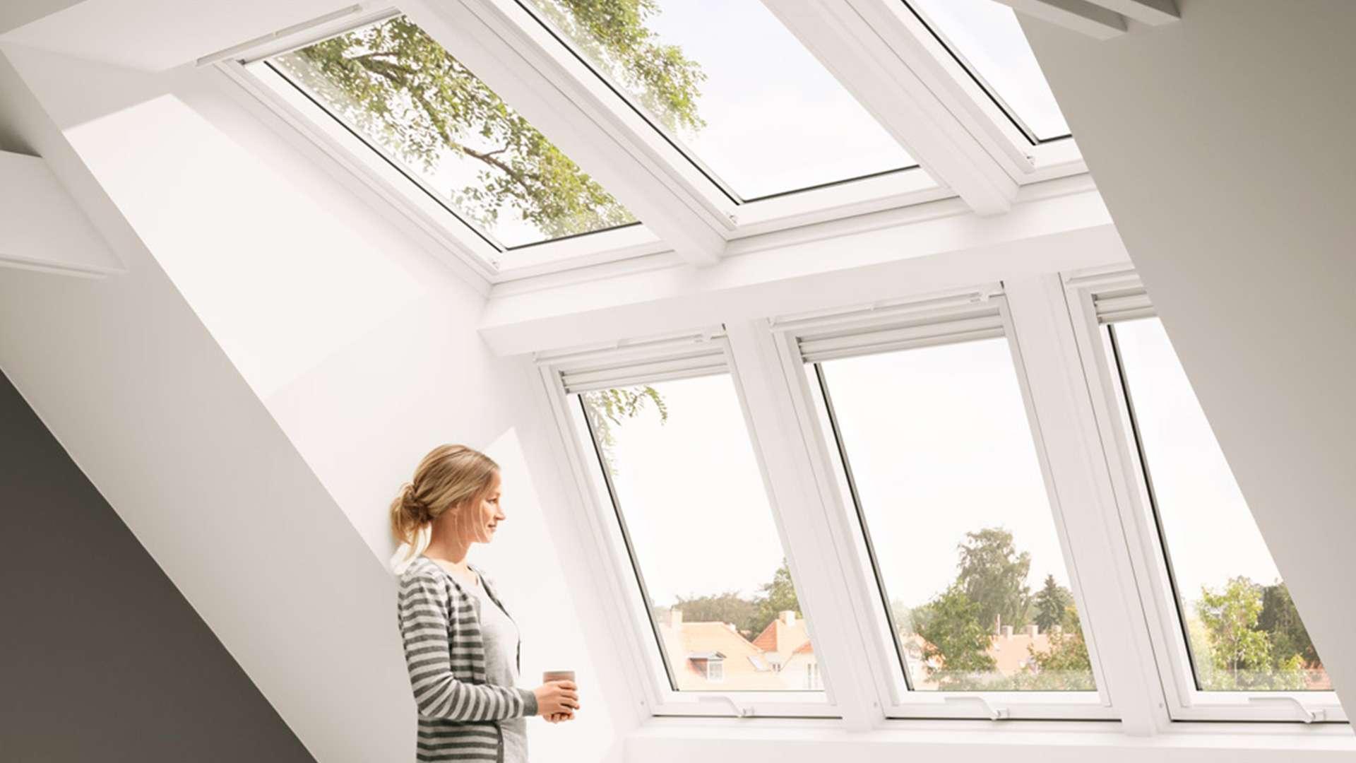 drei Dachfenster durch die eine Frau nach draußen scheint