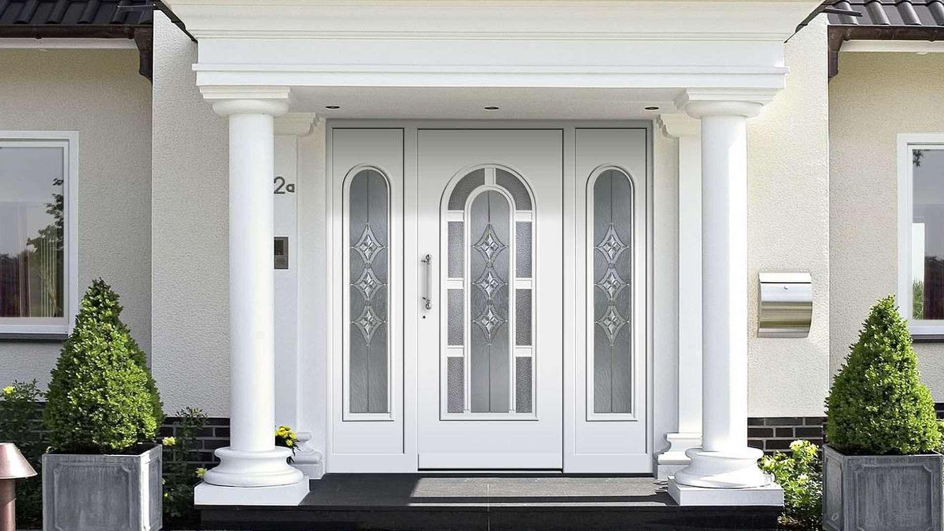 weiße Haustür mit Glaselementen auf beiden Seiten und zwei Säulen vor dem Eingang an einem hellen haus