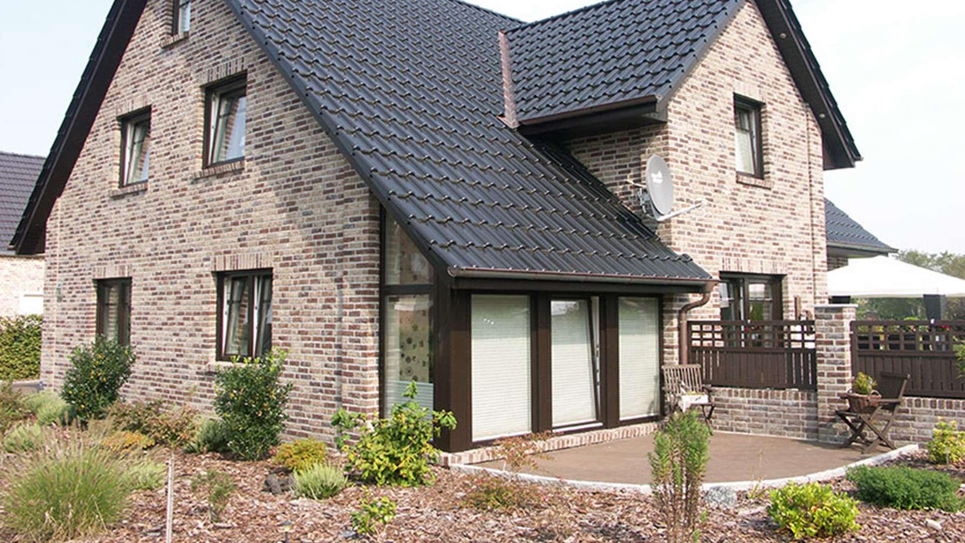 Einfamilienhaus mit Haustür und vielen Fenstern