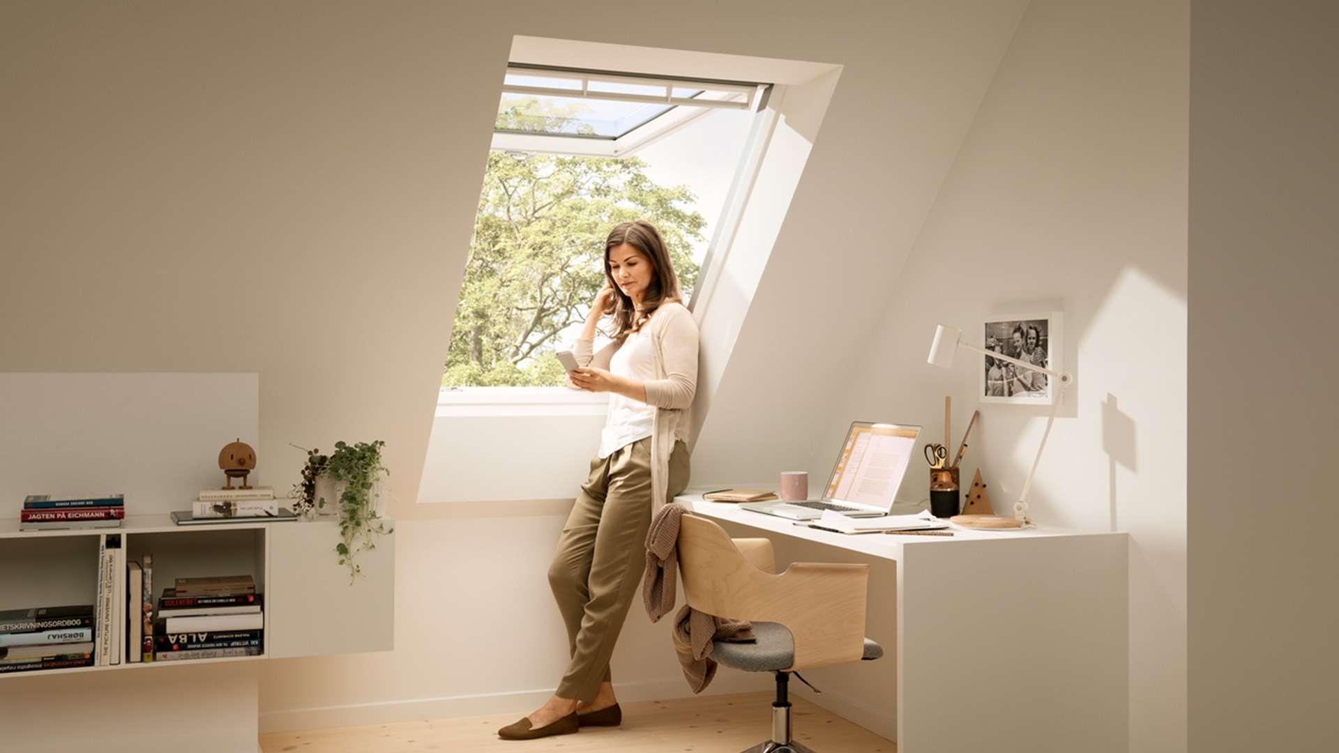 offenes Klapp-Schwing-Fenster in einer Dachschräge wo eine Frau steht