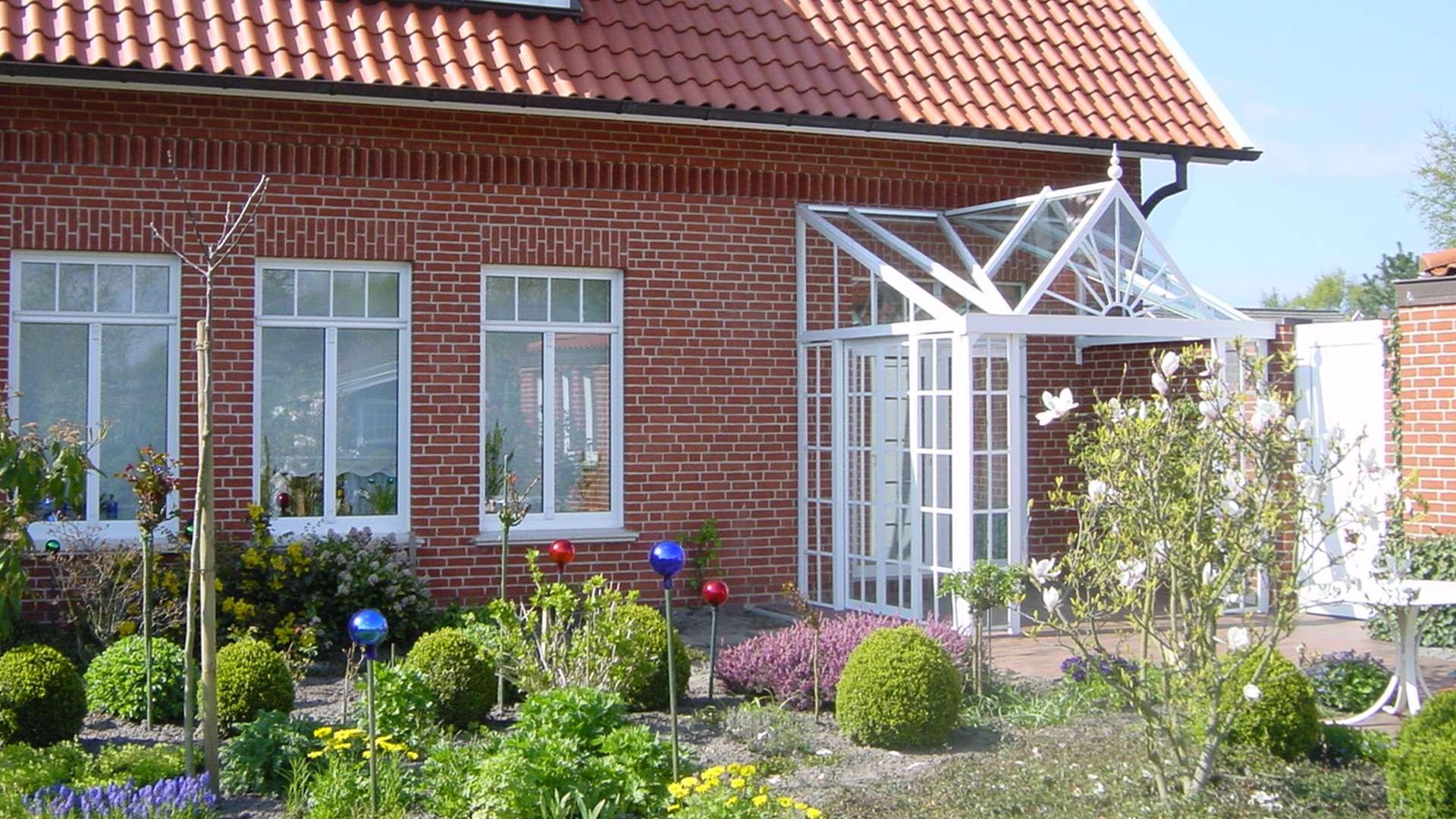 weißer Wintergartenvorbau über der Haustür eines Wohnhauses