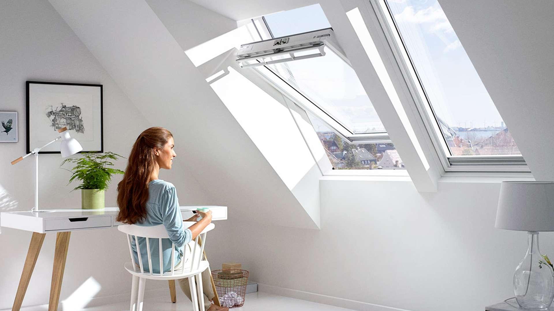 Frau sitzt unter einem geöffneten Schwingfenster im Dachgeschoss