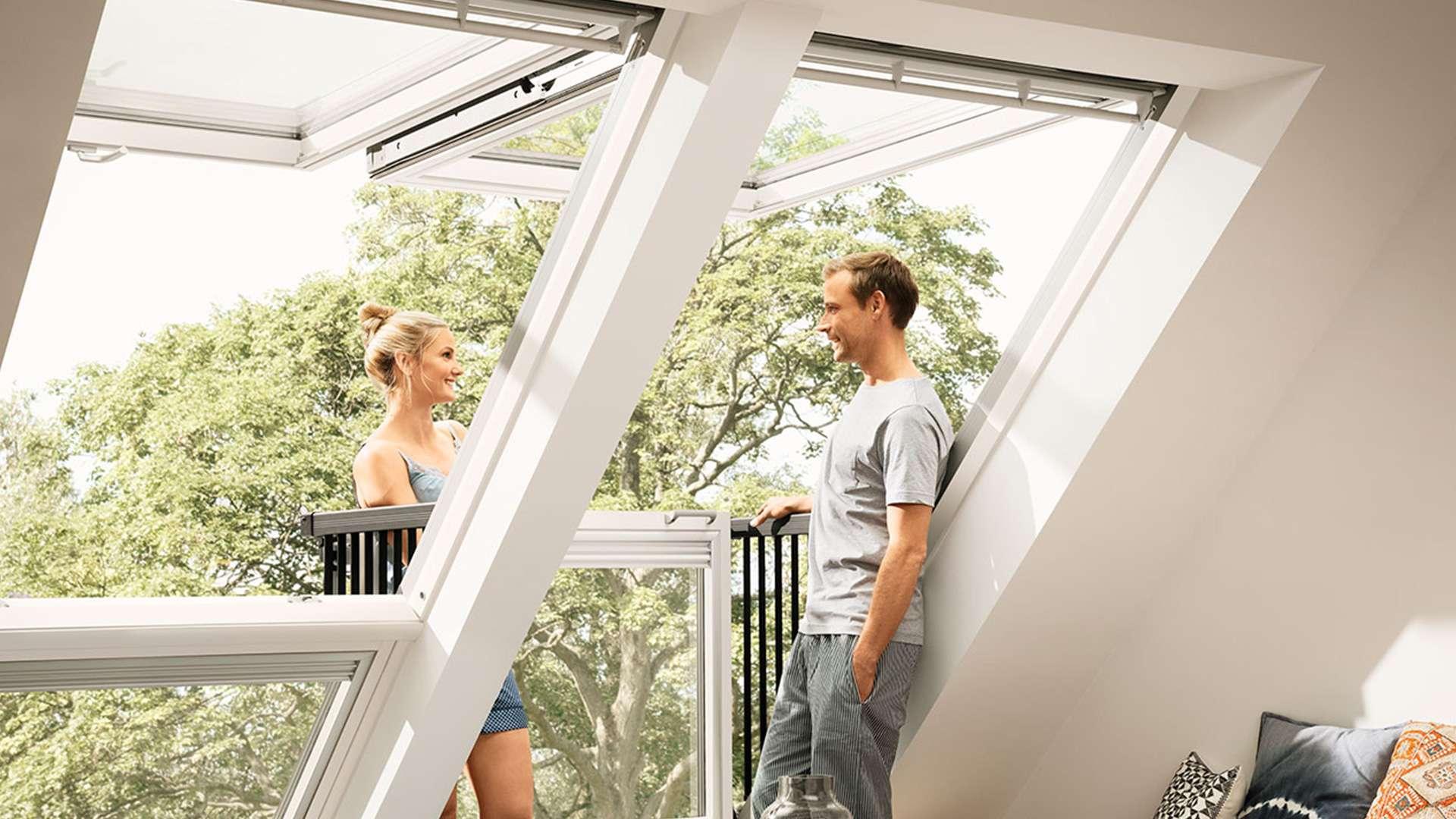 Pärchen steht in einem  VELUX CABRIO™ Dachfenster