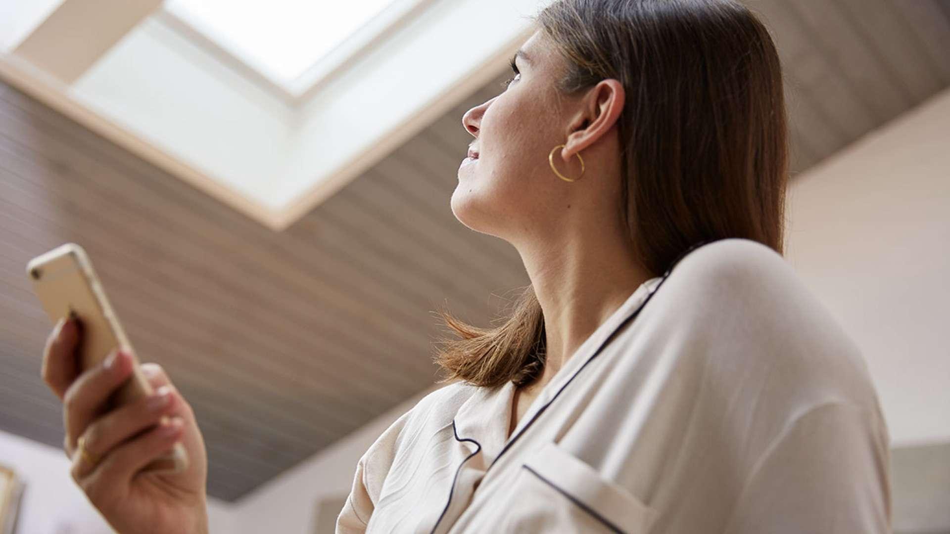 Frau öffnet ein VELUX INTEGRA® Dachfenster mit einer Fernbedienung