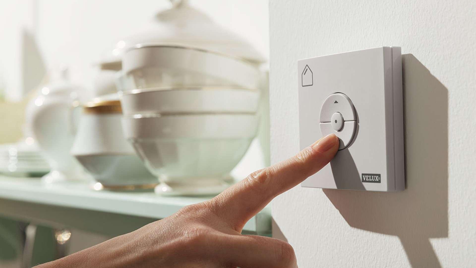 Hand bedient ein VELUX INTEGRA® Fenster mit einem Schalter an der Wand