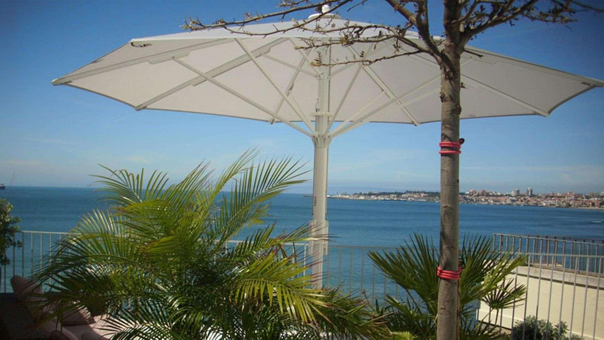 Sonnenschirm am Meer mit Palmen