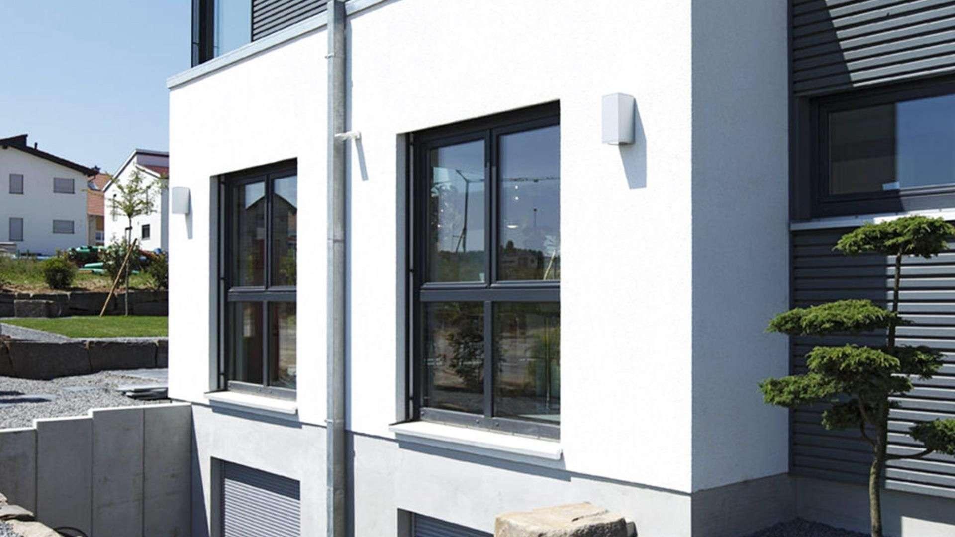 zwei schwarze Fenster in weißer Fassade