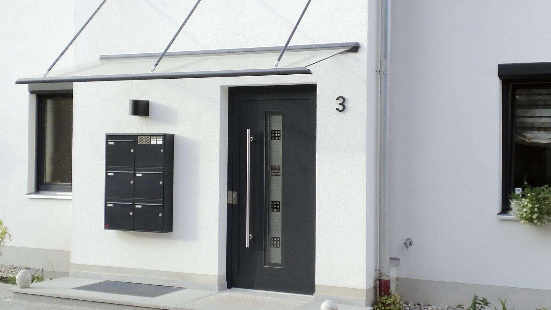 Eine schwarze Haustür als Kontrast zur weißen Fassade.