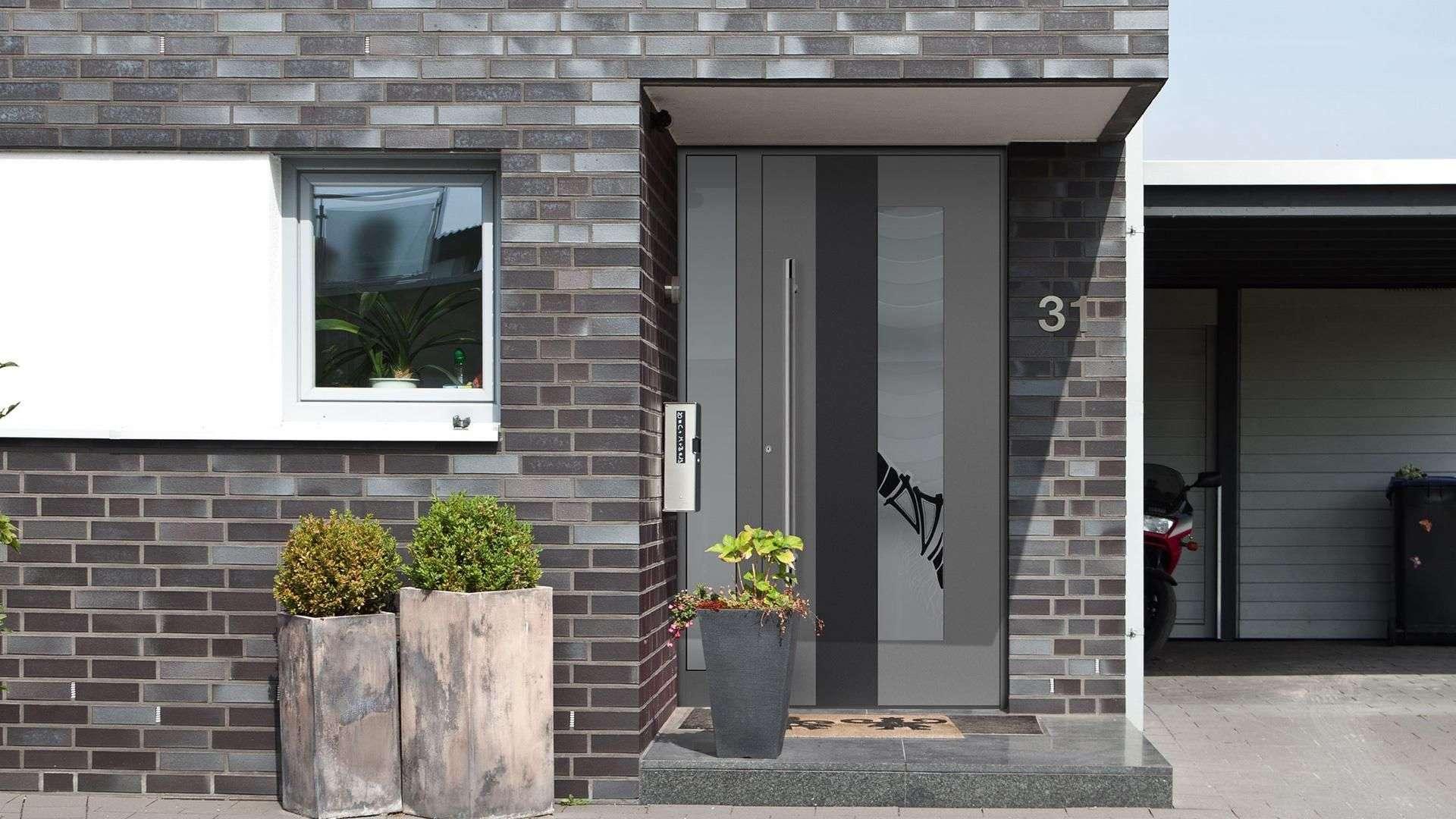Graue Haustür im grauen Ziegelsteinhaus