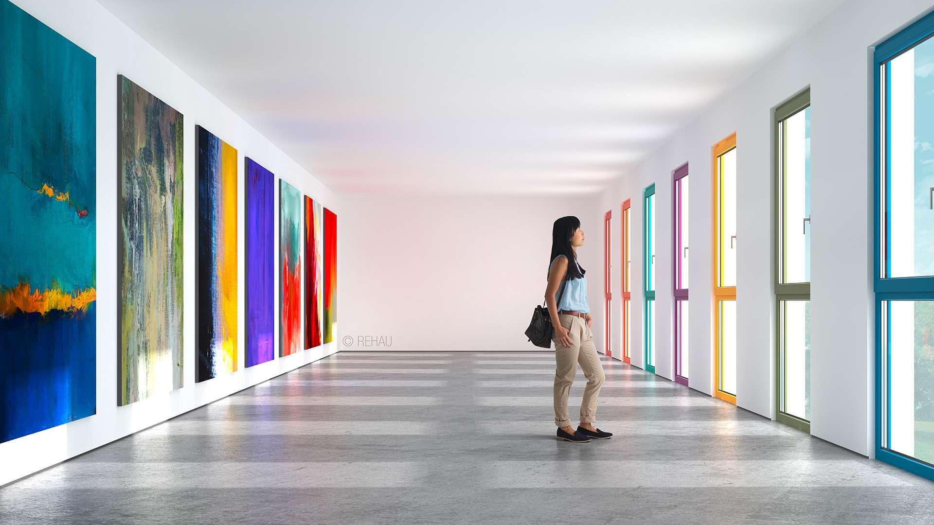 Frau in einer Galerie mit bunten Bildern und bunten Fenstern
