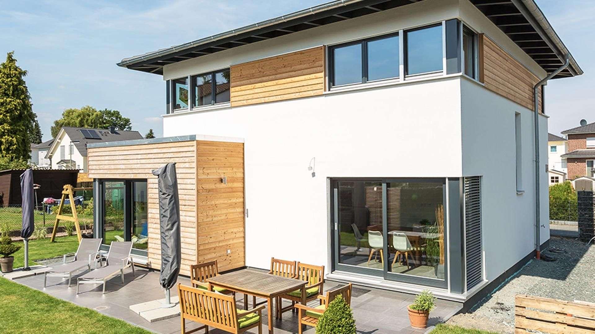 weißes Haus mit Flachdach, Holzakzenten und Terrasse
