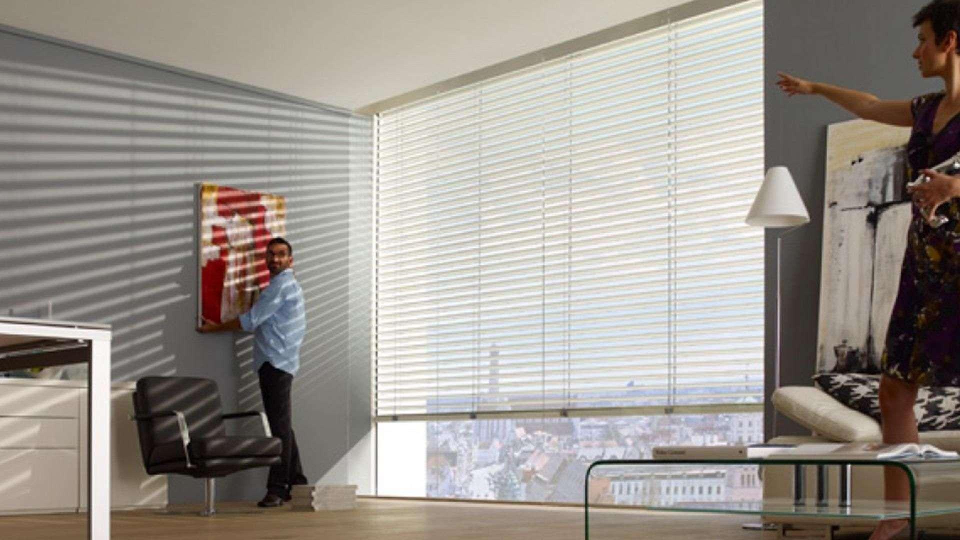 Mann im Raum vor großem Fenster mit halb runtergelassener Jalousie