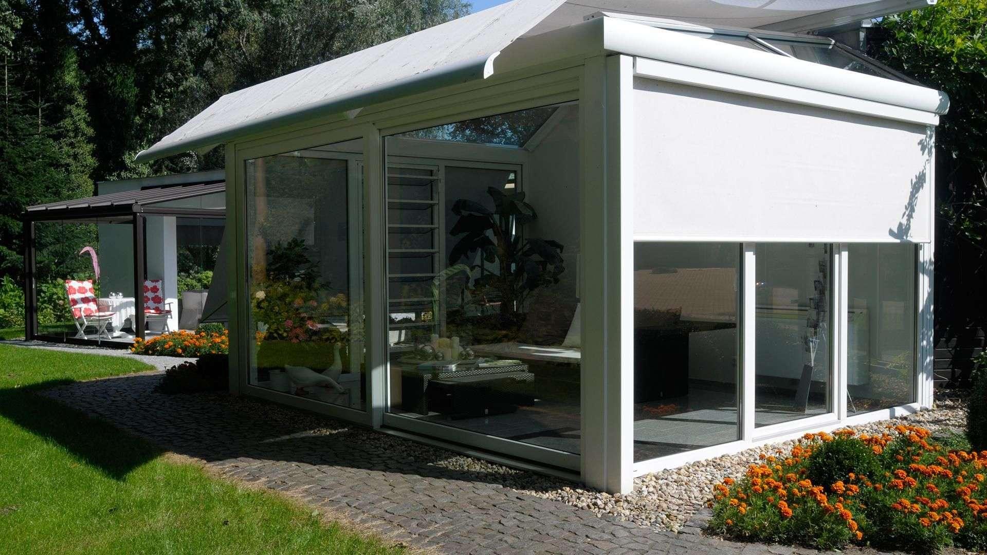 Wintergarten in der Ausstellung von Dürbusch. Vollständig verglast mit weißem Rahmen und Sonnenschutz.