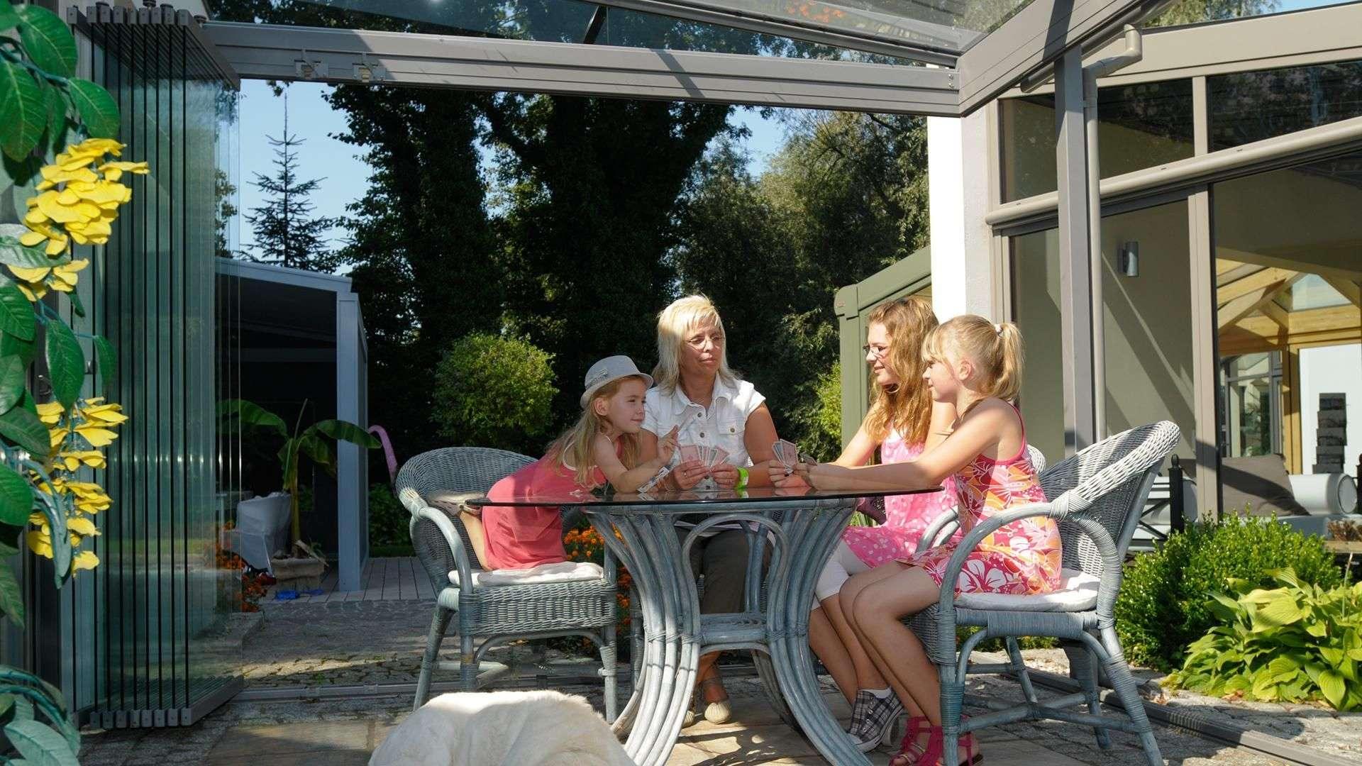Familie sitzt am Tisch im Wintergarten