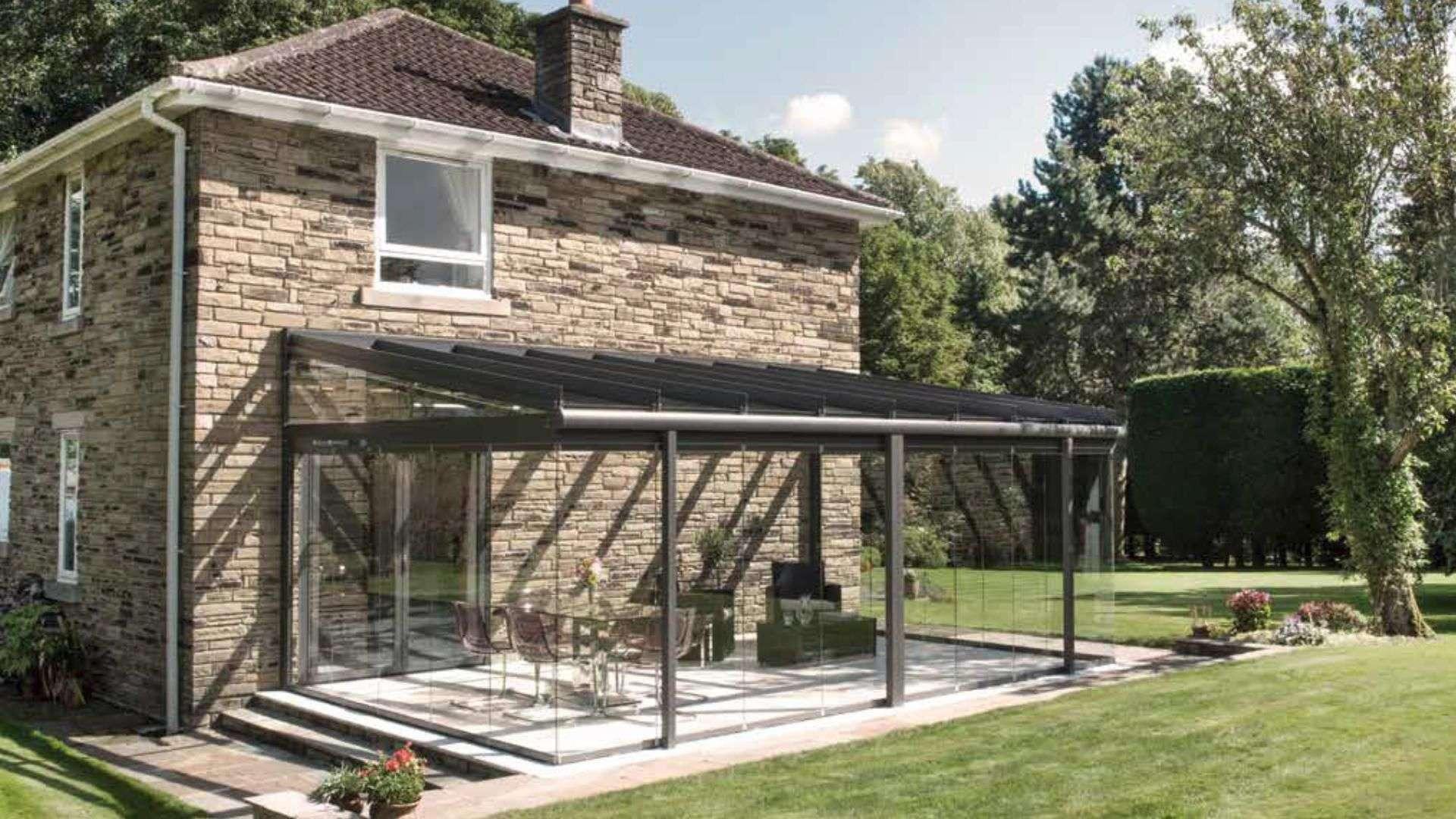 Haus aus Stein mir grauem Glashaus auf der Terrasse