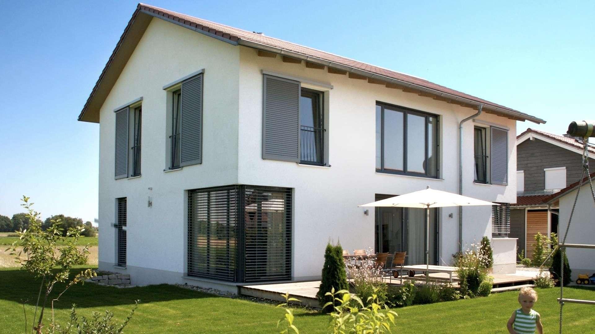 weißes Einfamilienhaus mit großen Garten