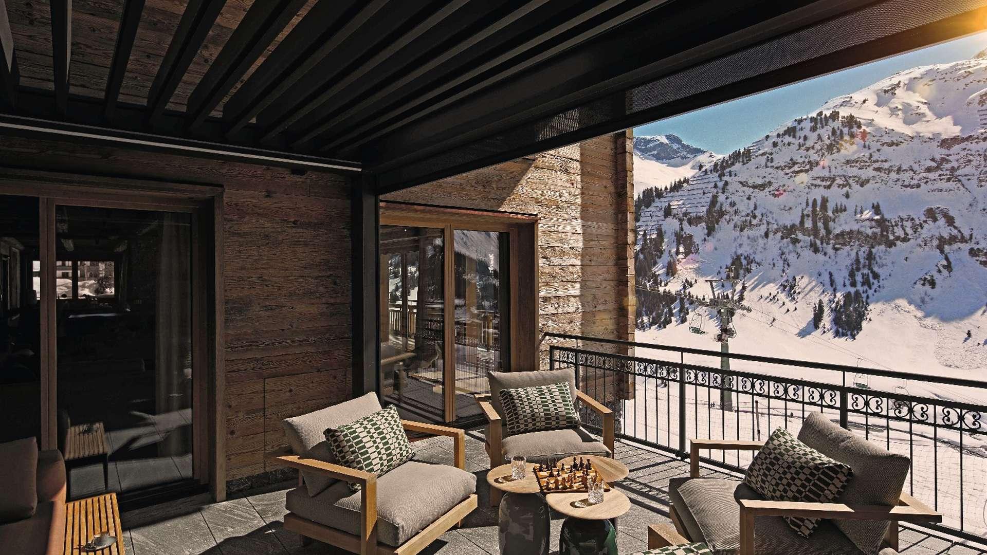 Lamellendach mit Sitzmöbeln darunter und Blick in den Schnee